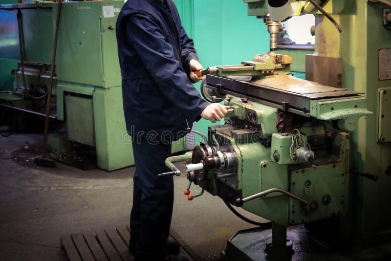 一名男性工作者在一台更大的金属铁锁匠车床,修理的设备,金属工作工作在冶金的一个车间 库存照片
