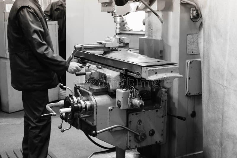 一名男性工作者在一台更大的金属铁锁匠车床,修理的设备,金属工作工作在冶金的一个车间 库存图片
