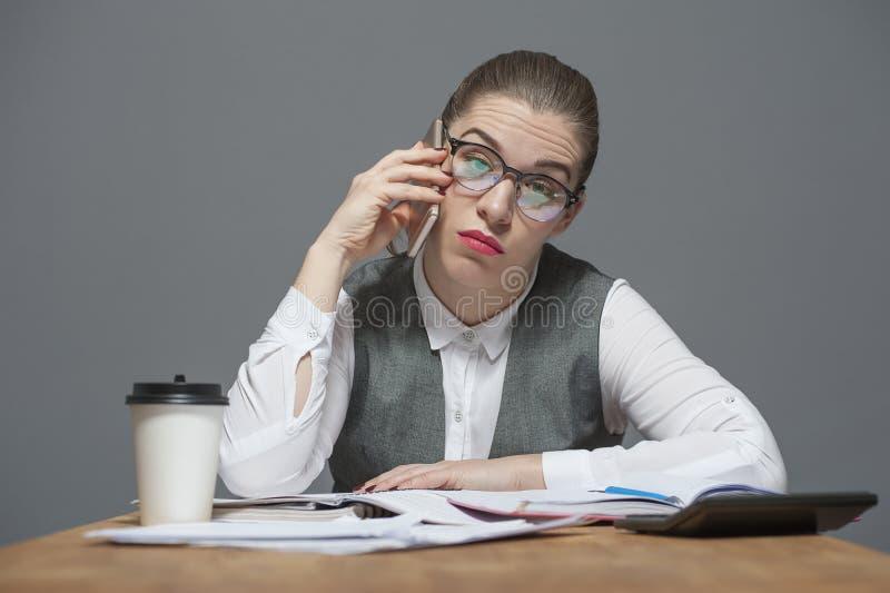 一名疲乏的女实业家在电话谈话 免版税库存图片