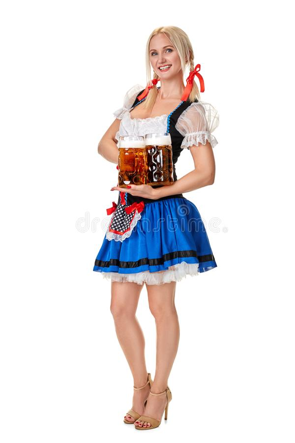 一名白肤金发的妇女的全长画象有拿着啤酒杯的传统服装的被隔绝在白色背景 免版税图库摄影