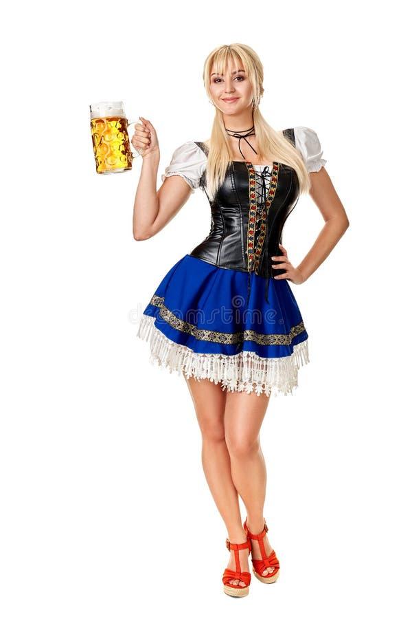 一名白肤金发的妇女的全长画象有拿着啤酒杯的传统服装的被隔绝在白色背景 库存照片