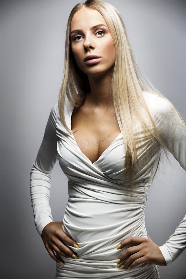 一名白肤金发的妇女的确信的时尚画象白色礼服的 免版税库存图片