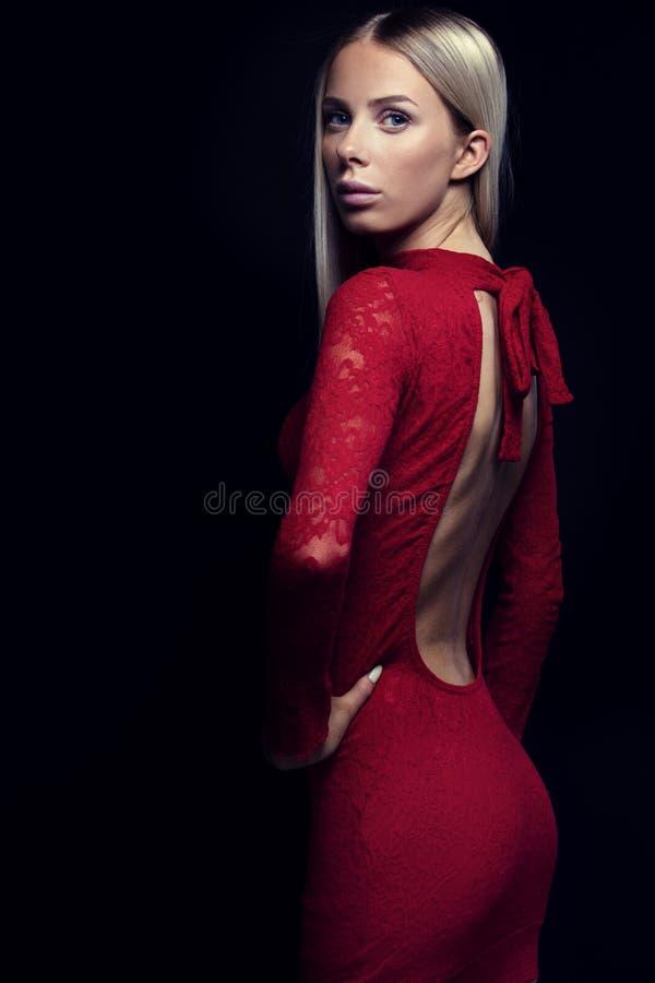 一名白肤金发的妇女的黑暗的画象红色礼服的 库存图片