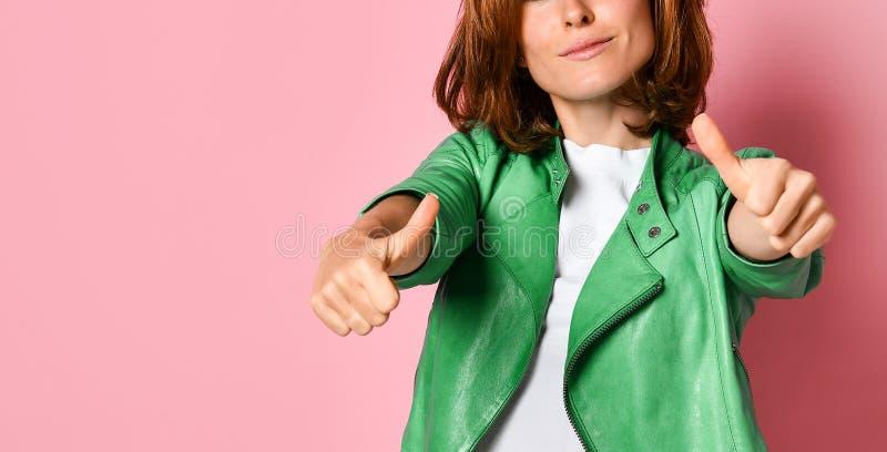 一名相当可爱的妇女的画象一绿色皮夹克的,显示赞许用在桃红色背景的两只手 免版税库存图片