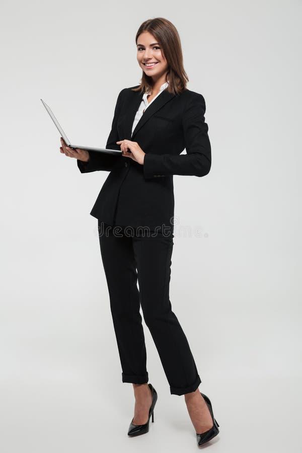 一名确信的微笑的女实业家的全长画象 库存图片
