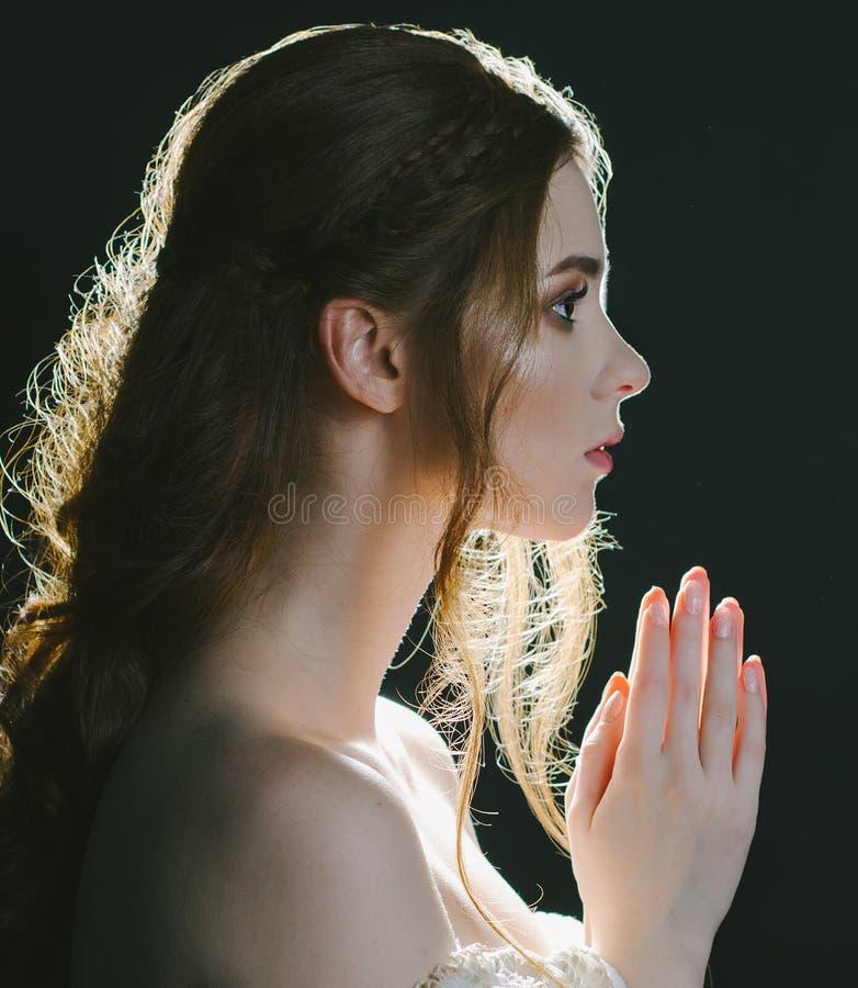 一名祈祷的年轻红发妇女的一张接近的画象葡萄酒灰礼服的有在黑背景的开放肩膀的在背后照明 图库摄影