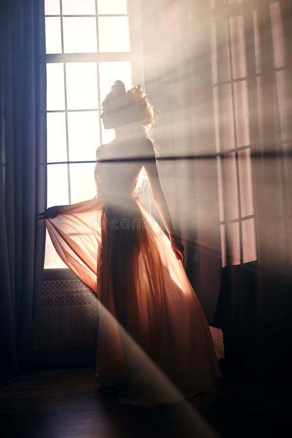 一名神奇神仙的妇女的剪影窗口的背景的在阳光下 女孩在清早的阳光下 免版税库存图片