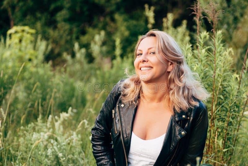 一名笑的妇女的画象一黑皮夹克的 r 免版税库存照片