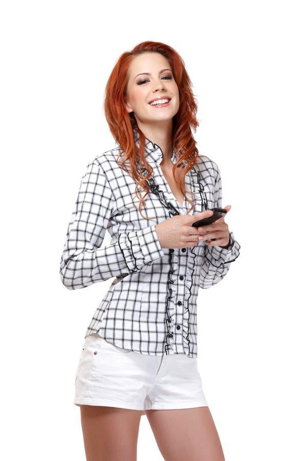 一名红头发人妇女的纵向有移动电话的 库存图片