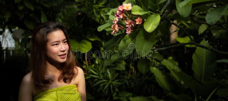一名美丽的亚裔妇女在庭院里看桃红色花 库存图片
