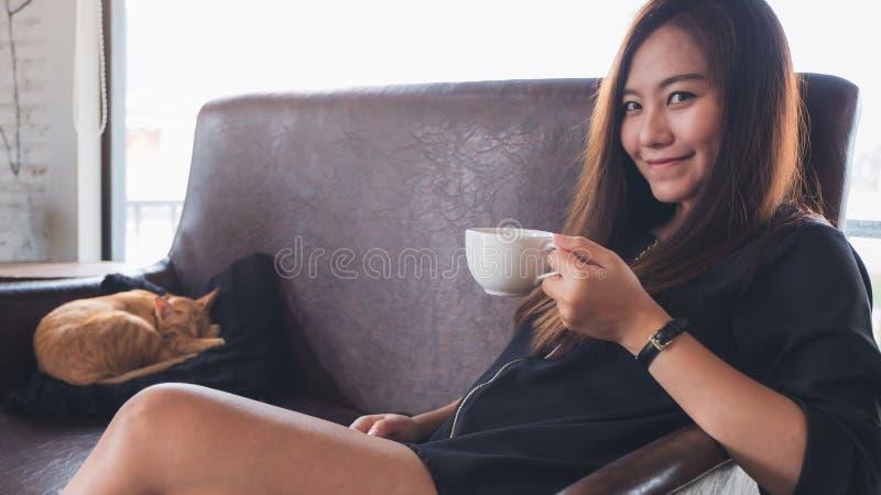 一名美丽的亚裔妇女坐沙发,当一只小的棕色猫在一个黑枕头时睡觉 免版税库存图片