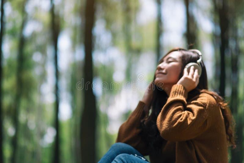 一名美丽的亚裔妇女的模糊的照片喜欢听到与耳机的音乐 库存图片