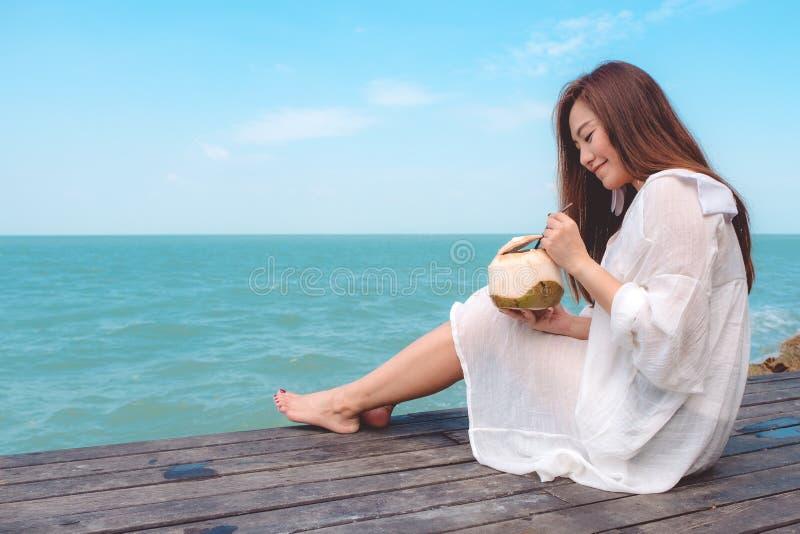 一名美丽的亚裔妇女的画象图象白色礼服开会的和喜欢喝在木阳台的椰子汁 免版税库存照片