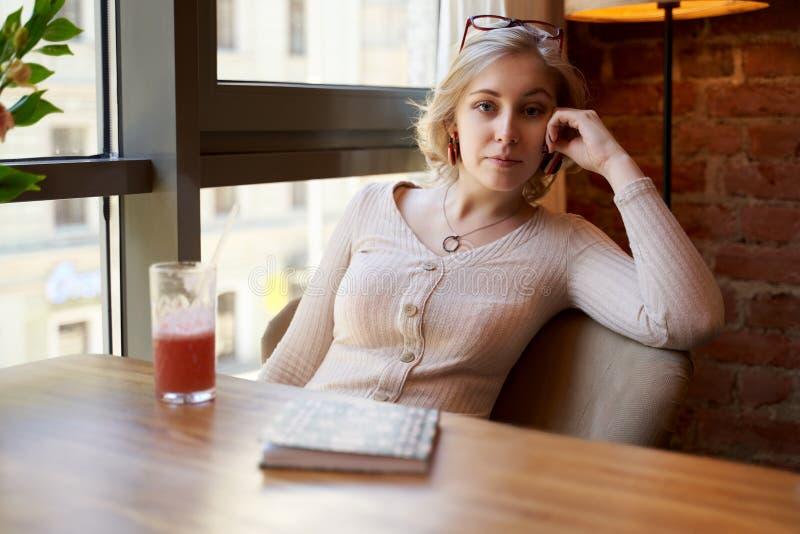 一名美丽的作家妇女在椅子倾斜了她的手肘,看与宜人的神色的照相机 免版税库存照片