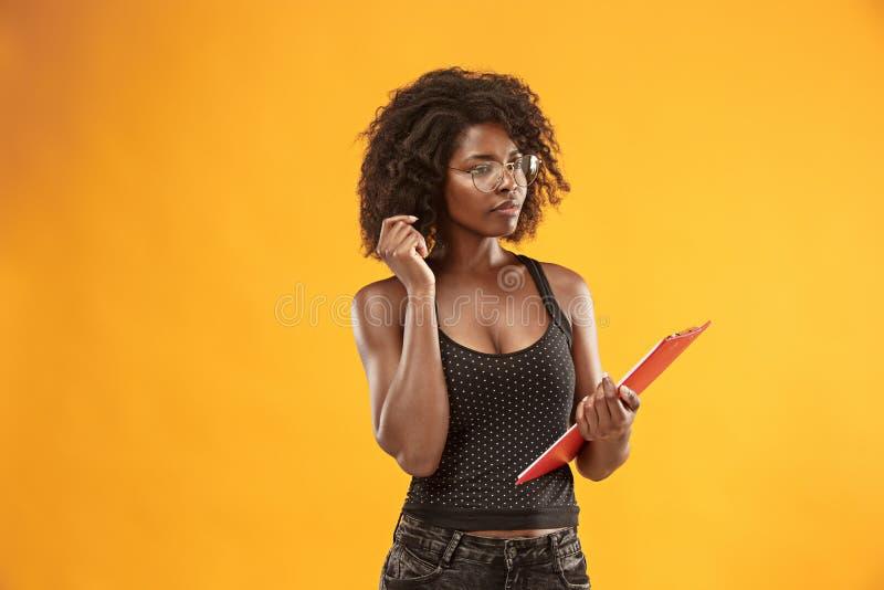 一名美丽的友好的非裔美国人的妇女的画象有一个卷曲非洲的发型和红色文件夹的 免版税库存照片