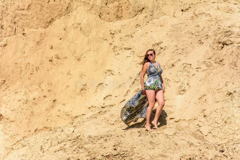 一名美丽的妇女在礼服和太阳镜站立反对一座含沙山 库存图片