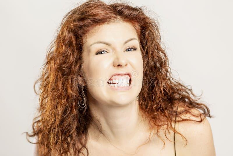 一名美丽的妇女是恼怒与恼怒的咧嘴 免版税图库摄影