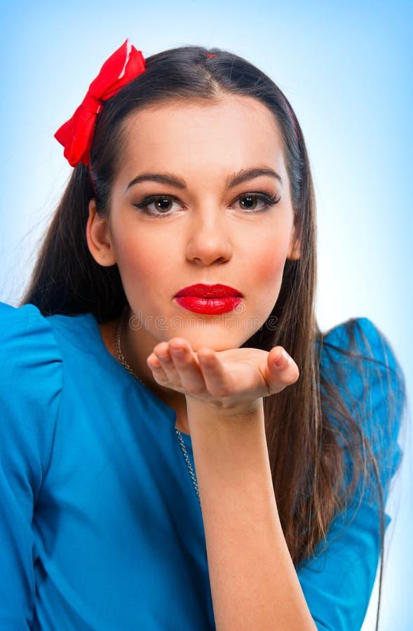 一名美丽的妇女的纵向发送亲吻的蓝色的 库存图片