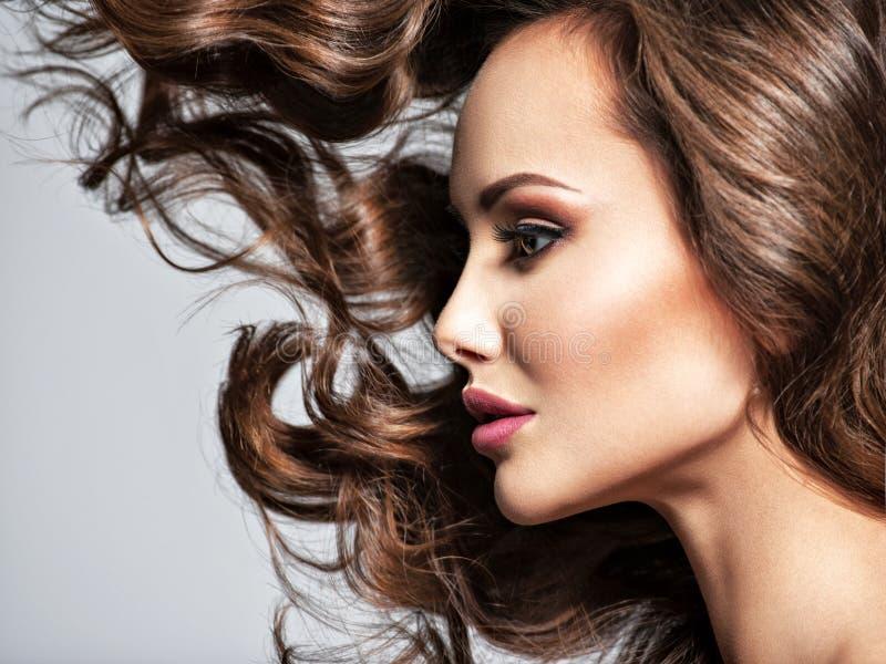 一名美丽的妇女的面孔有长的飞行头发的 免版税库存图片