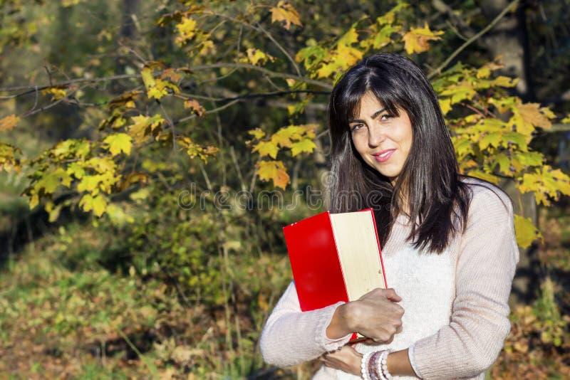 一名美丽的妇女的画象在秋天公园,拿着书 免版税库存图片