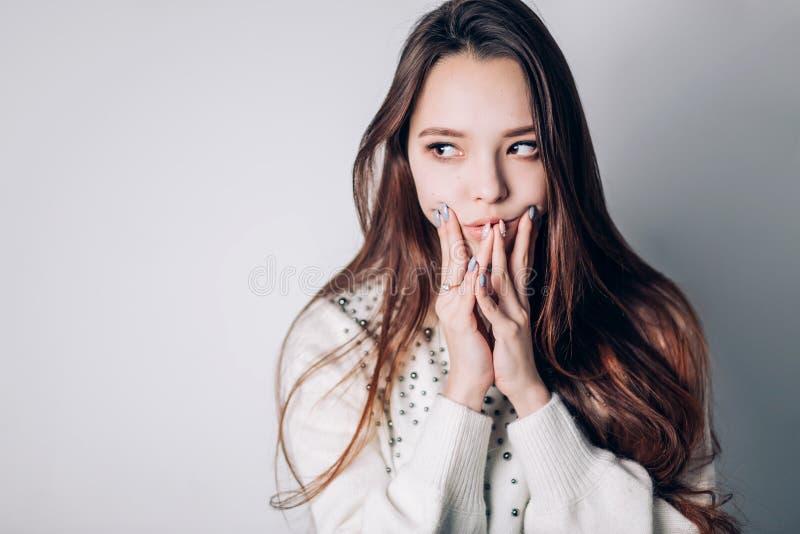 一名美丽的妇女考虑什么她计划,作梦 在面颊的手,看对在白色背景的边 库存照片