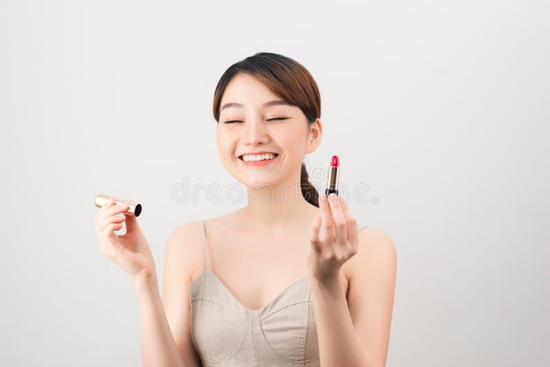 一名美丽的年轻俏丽的亚裔妇女的照片有摆在赤裸的健康皮肤的被隔绝在拿着唇膏的白色墙壁背景 免版税库存照片