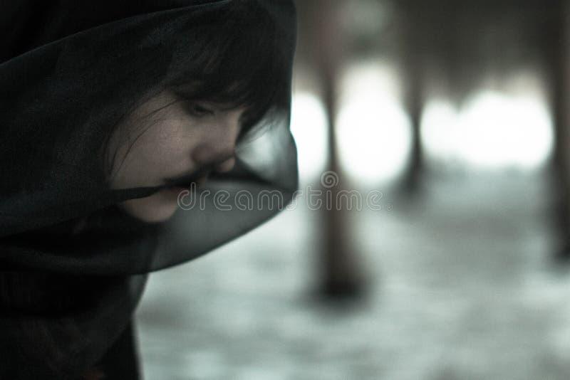 一名美丽的年轻单身妇女的特写镜头面孔消沉的在黑面纱,在一个黑白概念 免版税库存照片