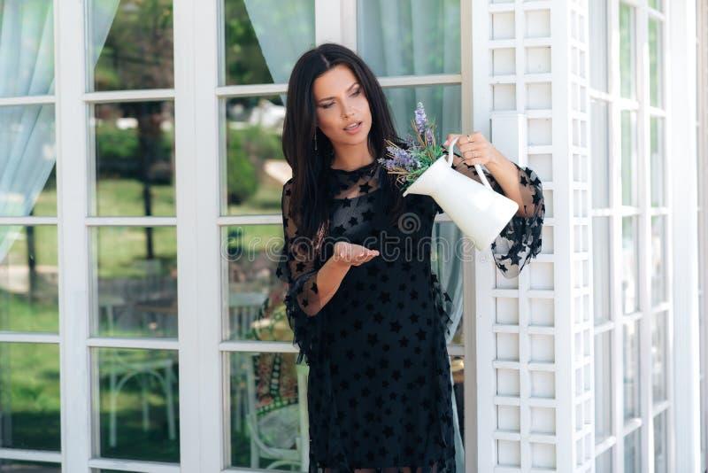 一名美丽的年轻欧洲妇女检查看是否有在一个花瓶的水花 女孩掀动了有的花瓶 库存图片