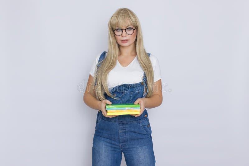 一名美丽的年轻白肤金发的妇女的演播室画象蓝色牛仔布总体和玻璃的在她的手上的拿着书在灰色 图库摄影