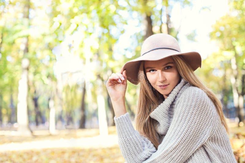 一名美丽的年轻白肤金发的妇女的画象有发光的直发的在一个棕色帽子在公园 库存图片