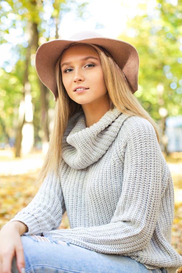 一名美丽的年轻白肤金发的妇女的画象有发光的直发的在一个棕色帽子在公园 免版税库存照片
