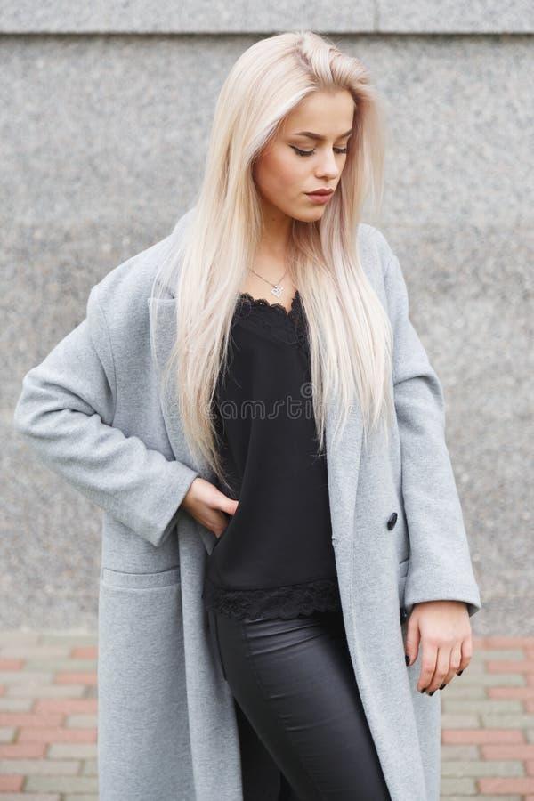 一名美丽的年轻白肤金发的妇女的画象灰色外套和黑皮革裤子的 街道时尚神色 免版税图库摄影
