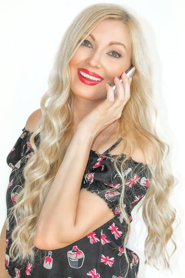 一名美丽的年轻白肤金发的妇女,当长发,谈话在逗人喜爱的手机和微笑 免版税库存照片