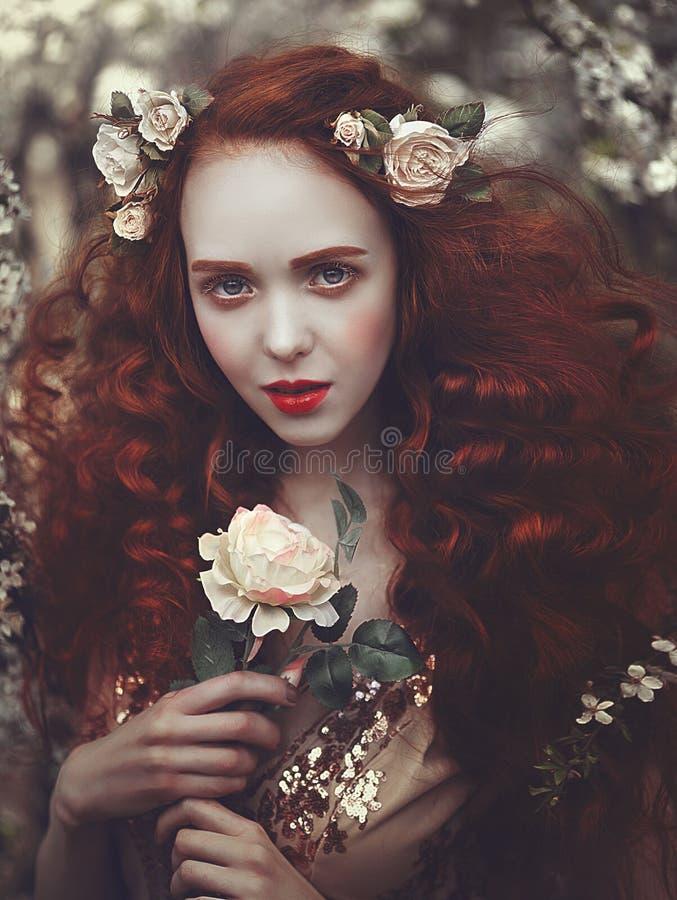 一名美丽的年轻肉欲的妇女的画象有非常长的红色卷发的在春天开花 春天的颜色 库存照片