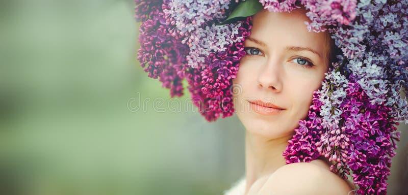 一名美丽的年轻蓝眼睛的妇女的室外时尚照片 春天颜色 淡紫色花的美丽的白肤金发的女孩 与s的香水 库存照片