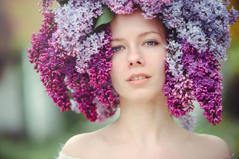 一名美丽的年轻蓝眼睛的妇女的室外时尚照片 春天颜色 淡紫色花的美丽的白肤金发的女孩 与s的香水 免版税库存图片