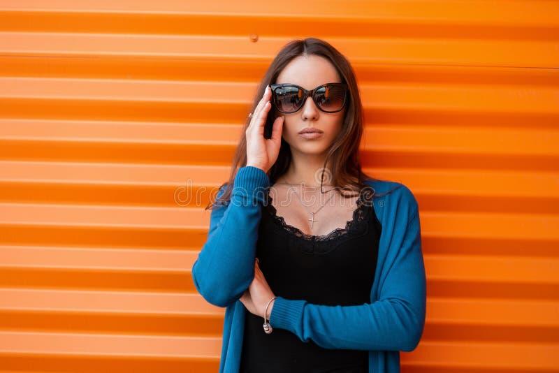 一名美丽的年轻行家妇女的画象有性感的嘴唇的在一件黑时髦的T恤杉的被编织的蓝色时髦的海角 免版税库存照片