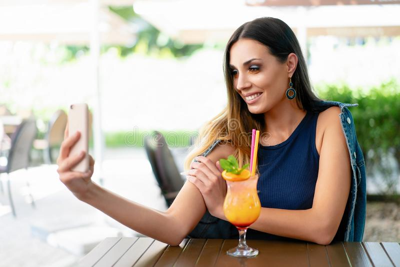 一名美丽的微笑的妇女在一家室外餐馆喝着一个异乎寻常的鸡尾酒和拿着一个手机 图库摄影