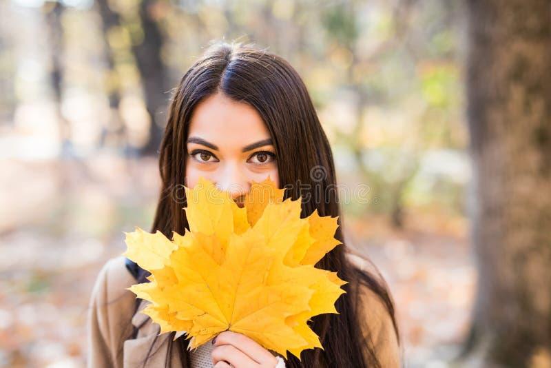 一名美丽的愉快的妇女的画象有微笑的与秋天黄色叶子在公园 图库摄影