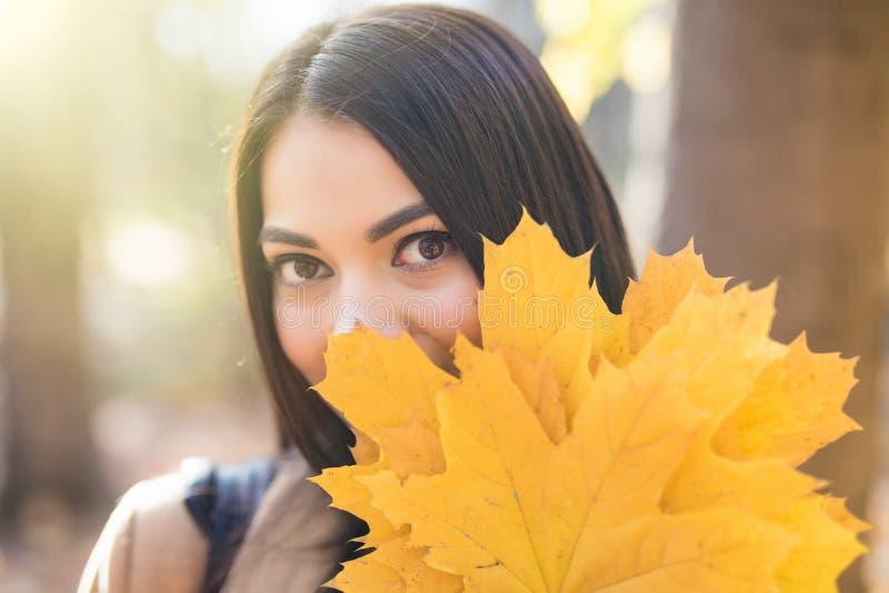 一名美丽的愉快的妇女的画象有微笑的与秋天黄色叶子在公园 免版税库存图片