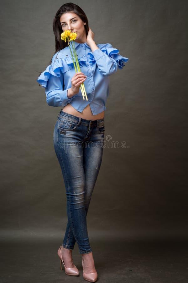 一名美丽的愉快的深色的妇女的画象拿着黄色jonquils在她的手上的蓝色衬衣的临近她的面孔 免版税库存照片