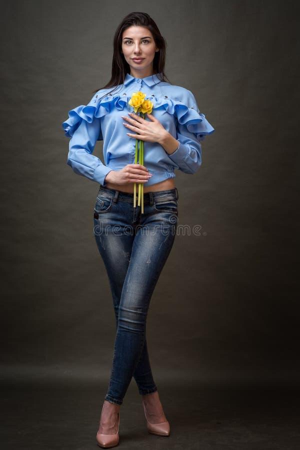 一名美丽的愉快的深色的妇女的画象蓝色衬衣的在她的手上的拿着黄色jonquils 库存照片
