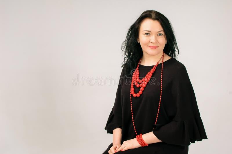一名美丽的深色头发的妇女接触她的头发 一张大画象 她在一件黑礼服打扮 她有红色种族 免版税库存照片