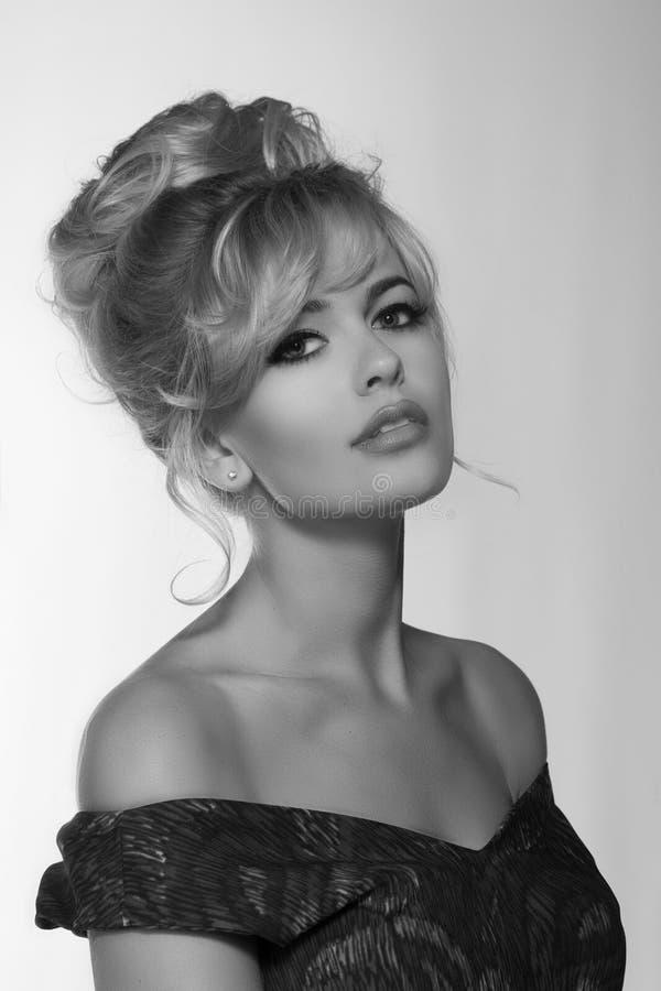 一名美丽的白肤金发的妇女的画象减速火箭的礼服50-s样式的 单色黑白照片 图库摄影