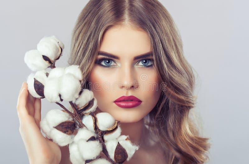 一名美丽的白肤金发的妇女的画象有一种发型的与卷毛和美好的构成,与棉花花在她的手上 免版税图库摄影