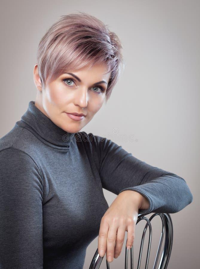 一名美丽的白肤金发的妇女的画象有美好的构成和短的理发的在染头发以后 免版税图库摄影