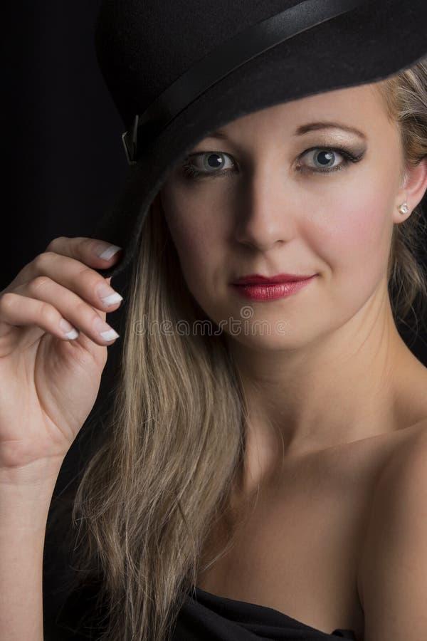 一名美丽的白肤金发的妇女的画象特写镜头有黑帽会议的 库存图片
