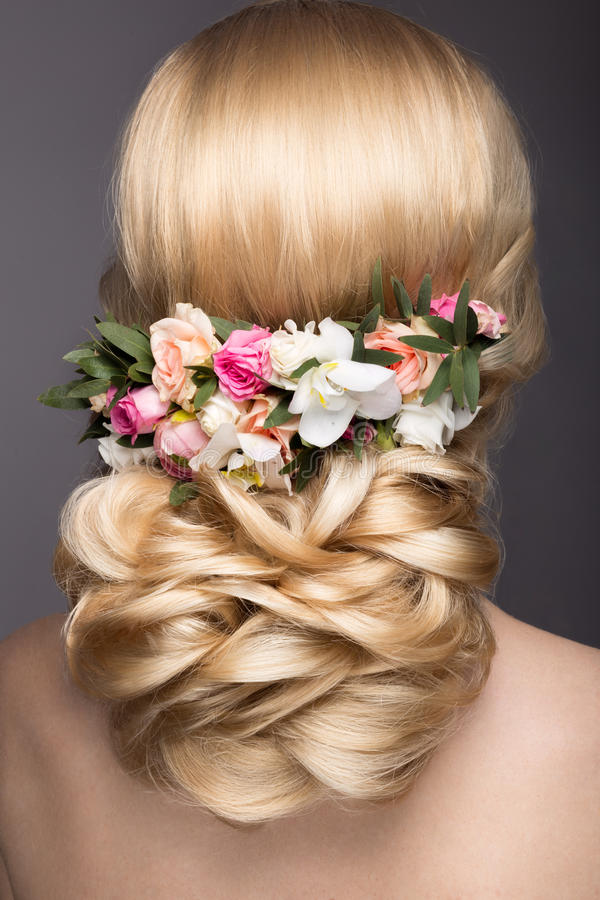 一名美丽的白肤金发的妇女的画象新娘的图象的有花的在她的头发 秀丽表面 发型后面视图 免版税库存图片