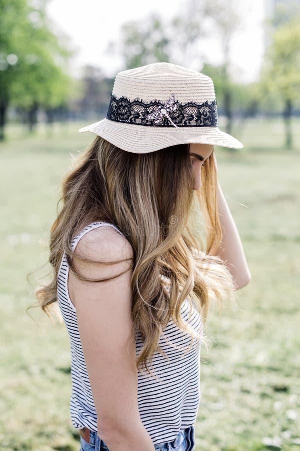 一名美丽的端庄的妇女的画象有摆在同水准的帽子的 库存图片