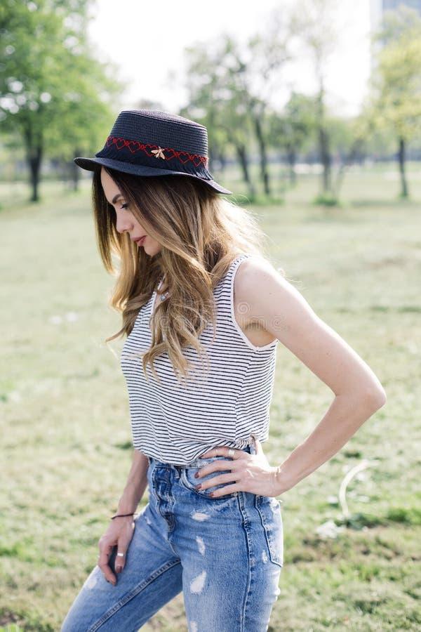 一名美丽的端庄的妇女的画象有摆在同水准的帽子的 免版税库存照片
